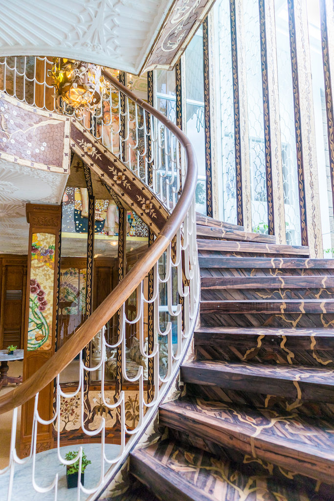 Casa Juico's wooden spiral staircase featuring images of creeping vines that leads to more function rooms