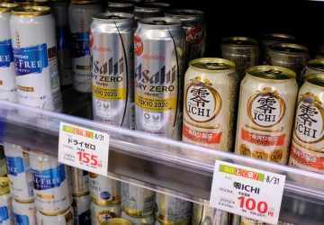 Various cans of alcohol-free beers are displayed on a supermarket shelf in Tokyo