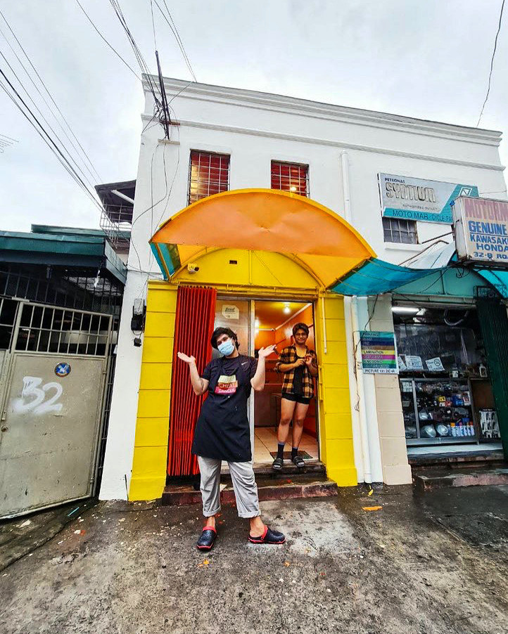 Miel Ochoa in front of Puesto Carinderia in Quezon City. To fund the renovation of the space, they collaborated with Silay-based artist Ginoe for their merch consisting of shirts, aprons, and tote bags