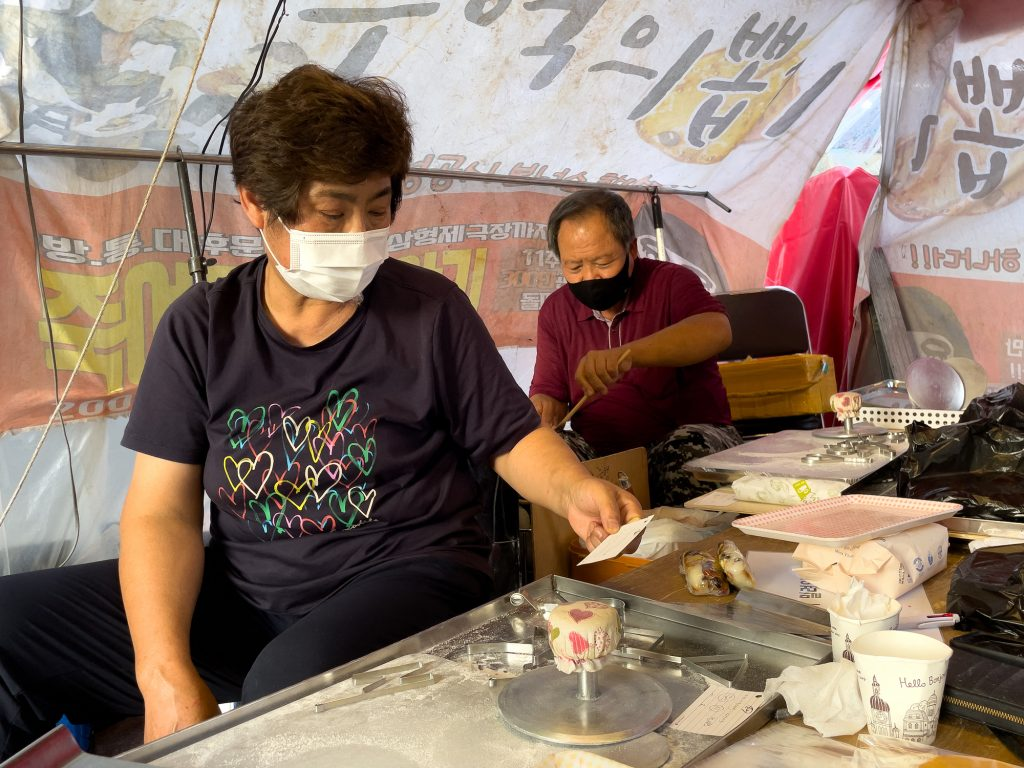 In this picture taken in Seoul on October 10, 2021, street vendor Jung Jung-soon (L) checks an order as her husband Lim Chang-joo (R) makes dalgonas, a crisp sugar candy featured in Squid Game