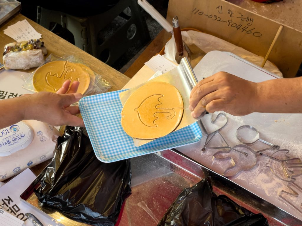 Street vendor Lim Chang-joo passes a dalgona for wrapping, a crisp sugar candy featured in 'Squid Game,' for which he and his wife Jung Jung-soon were hired to be on set to make during production